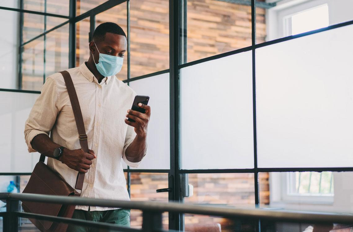 Man wearing face mask and looking at phone